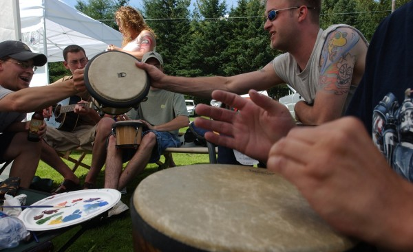 Keith Lohouse (left) hands off drumming duties to Dan Williams (second from right) as the duo join other traveling companions from Rochester, N.Y. for music and body painting at East Gate Trailer Park in Limestone in August 2003. The park served as a makeshift campground for Phish fans wanting to be first through the gates to Loring Commerce Centre.
