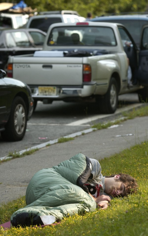 Ted LaBelle, of Milwaukee, takes a nap at the I-95N rest stop south of Medway as scores of Phish fans funnel through on their way to Loring in August 2003.