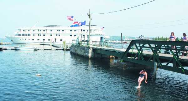 Shaydlyn Robinson, 14, of Owls Head, jumps off the Rockland Public Landing at high tide in 2011, as her friends looked on. The American Cruise Line ship The Independence docked in Rockland that summer.