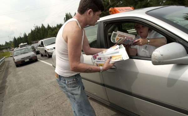 Mail carrier Nancy Theriault hands Norman Akerson of Caribou his mail in August 2003.  Theriault was stuck in traffic on Route 89 in Caribou, so locals came to her.