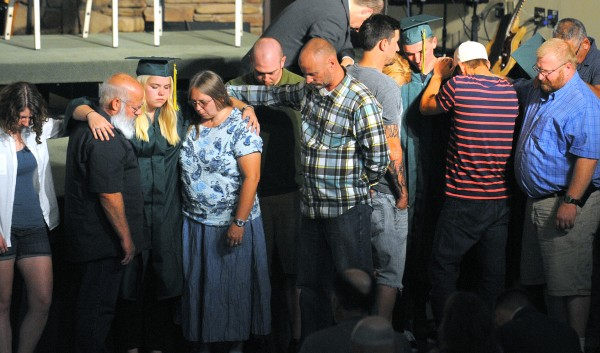 After the graduation ceremony was over, family, friends and teachers pray for the graduates at the Calvary Chapel Christian School in Orrington on Sunday. In 2013, only six students graduated, and due to financial difficulties the school is closing its doors.