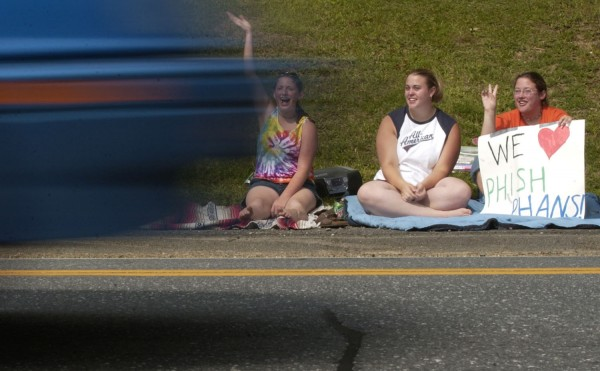 Poised along U.S. 1 in Monticello (from left), Bethany Targonski, Amanda Joslyn, and Alisha Targonski wave to Phish fans passing through town on their way to Loring in August 2003. Stopping midsentence to think, Alisha said, &quotThis is the biggest thing since - Lemonwheel.&quot