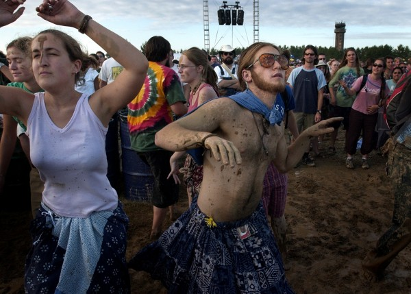 Abby Levin (left) and Brian Sprengelmeyer (center) dance in a mud pit in the concert area in August 2003. The mud at the Loring Commerce Centre was unavoidable, but many fans found ways to enjoy it.