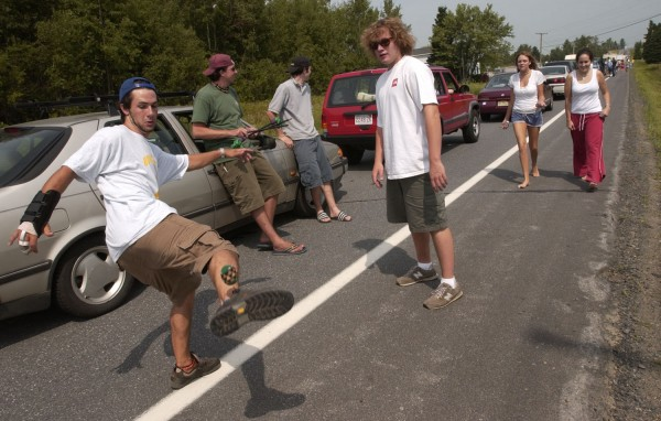Phish fans (from left) Jeff Kearns, 20, of Ringwood, NJ, Mike Law, 19, of Ringwood, NJ, John Shushereba, 18, of Essex Junction, VT, Tom Angelone, 19, of Ringwood, NJ, Megan Clas, 19, of Rochester, NY and Jessica Dinaburg, 18, of Rochester, NY, kill time as traffic remains at a stand still on Route 1A through Maple Grove in southern Fort Fairfield in August 2003.