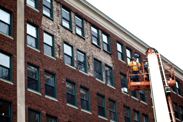 A workman rides a lift to the fifth and sixth floors above 142 High Street in Portland Monday afternoon where part of the brick facade separated from the building on Sunday.