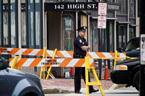 A Portland police officer keeps watch at the corner of High Street and Congress Street Monday. High Street to Deering Street was closed after part of a brick facade separated from the building at 142 High Street.