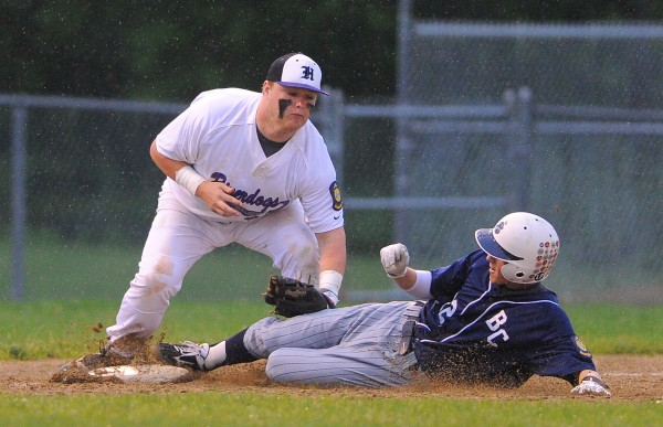Bangor's Carl Farnham (right) slides to third base, beating the tag by Hampden's Shawn Smith during their Zone 1 American Legion baseball game in Hampden Wednesday evening. The Comrades won 4-0.