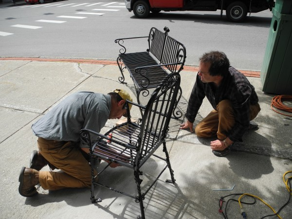 Wes Reddick (left) and Alan Curry fasten a bench and chair to the High Street sidewalk. Curry's installation, called &quotOld School,&quot is part of the 2013 rendition of &quotPlease, Be Seated,&quot a project that brings art in the form of chairs and benches to downtown Belfast.