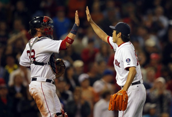 Boston Red Sox catcher Jarrod Saltalamacchia and pitcher Koji Uehara celebrate after the Red Sox beat the Toronto Blue Jays 7-4 Thursday night at Fenway Park in Boston.