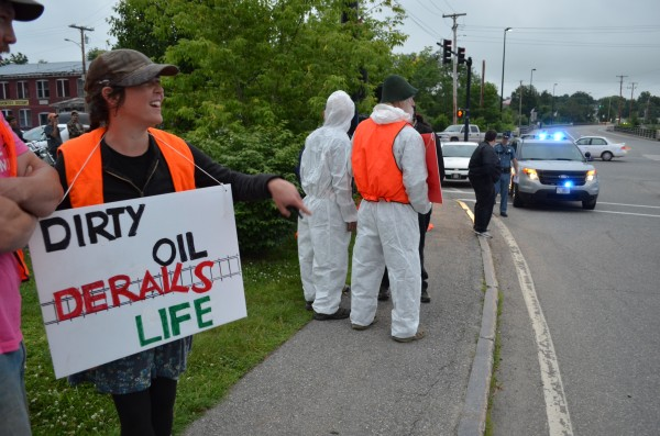 Meg Gilmartin of Belgrade (left) holds a sign in protest of fracked oil traveling through Maine during a demonstration on Lawrence Avenue on Thursday, June 27, 2013. Six protesters were arrested.