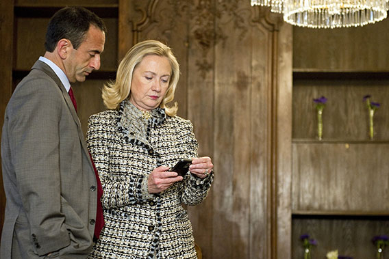 U.S. Secretary of State Hillary Clinton (R) looks at a phone message with Assistant Secretary of State for European Affairs Philip Gordon as they wait in a conference room for a bilateral meeting with Ukrainian President during the 48th Munich Security Conference at the Bayerischer Hof hotel in Munich, southern Germany, on February 4, 2012.