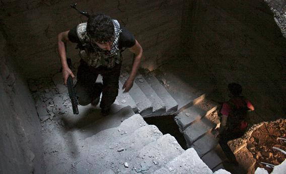 Free Syrian Army fighters run up the stairs of a building in Aleppo's Salaheddine neighborhood on April 28, 2013.