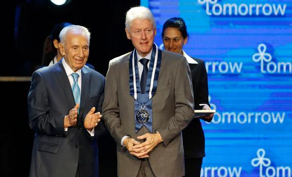 Israel's President Shimon Peres (L) stands with former U.S. President Bill Clinton after awarding him the Presidential Medal of Distinction at the fifth annual Presidential Conference in Jerusalem June 19, 2013.