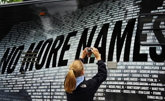 NEWTOWN, CT - JUNE 14: Lindsay Knauf takes a picture of a bus bearing some of the over 6,000 names of people killed by gun violence since the massacre in Newtown at a remembrance event on the six month anniversary of the massacre at Sandy Hook Elementary School.