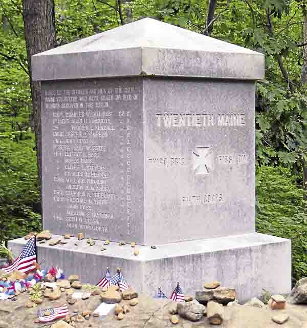 Mementos ranging from American flags to coins, flowers, and rocks surround the 20th Maine Infantry Regiment monument on Little Round Top in Gettysburg National Military Park in Pennsylvania. Regiment survivors erected the monument in autumn 1888.