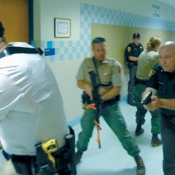 "Sagadahoc County Sheriff's Deputy Matt Sharpe, left, Marine Patrol Officer Matt Sinclair (center, blurry), Sagadahoc County Chief Deputy Brett Strout, and in rear, DeniAnne Kilgore, work as a team moving through the hallway of Bowdoinham Community School during a training Monday in search of a ""shooter."" Lt. Calvin Temple of Sagadahoc County Sheriff's Department observes at the far rear. Below, Strout moves through a classroom door as his team searches for a hypothetical ""shooter."""