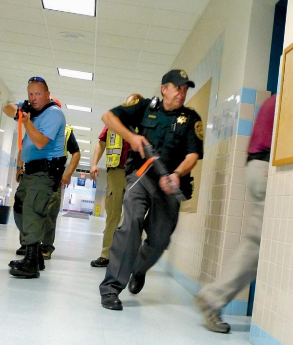Sagadahoc County Sheriff's Department Sgt. Gregory Siegel is through the doorway followed by Lt. Calvin Temple while Cpl. Ian Alexander covers the hallway checking for shooters during a training at Bowdoinham Community School Monday.
