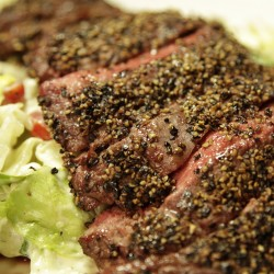 Serve the steak warm over the salad.