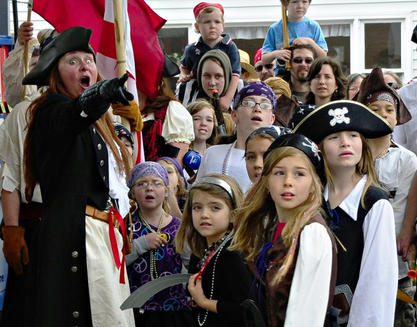 """Bloodthirsty Barbara"" (left), from Pirates of the Dark Rose crew, points out the Damariscotta Bank & Trust to a crew of children, where the pirates go to ""extort"" treasure through the drive-up station. (Photo by Don Dunbar/easternmaineimages.com)"