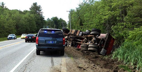 Police on scene after a collision with another vehicle caused a truck to roll over on Route 4 in Turner on Friday.