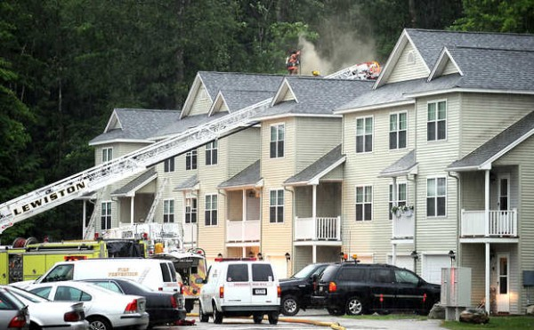 Lewiston firefighters work in the pouring rain to contain a fire on Ledges Court on Tuesday evening.