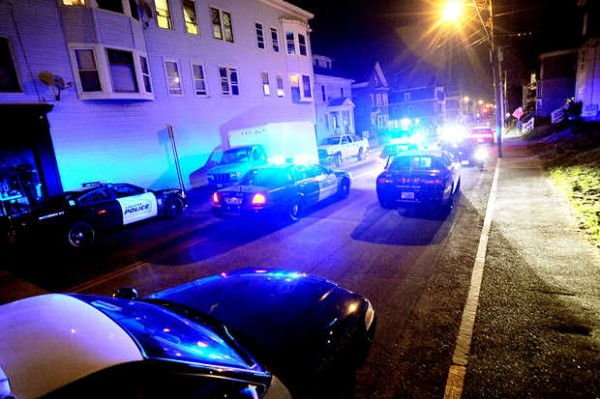 Police flock to the building at left on Bartlett Street in Lewiston on Thursday.