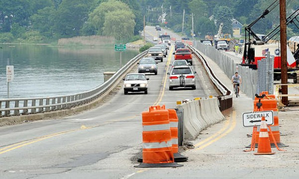 A cyclist uses the sidewalk during the Martin's Point Bridge construction on Route 1 between Falmouth and Portland on Wednesday. An altercation between a motorist and a cyclist has raised awareness of the hazardous conditions of using the popular commuter route.