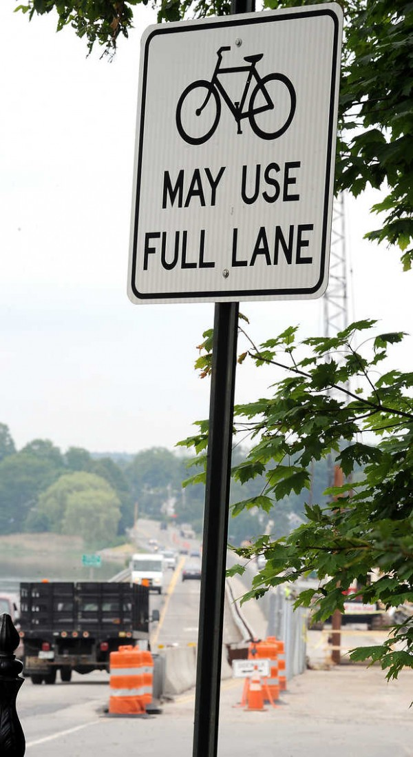 A sign at the start of Martin's Point Bridge in Portland warns motorists that cyclists can use the entire lane to cross the busy Route 1 construction area.