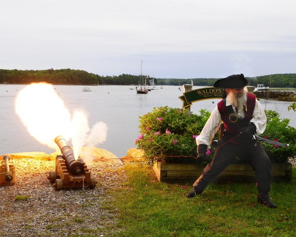 """Doc"", from Pirates of the Dark Rose crew, discharges ""Leaping Louis"" a six-pound naval gun located on Battery Point (he Mattson Marina in Newcastle). His target is the pirate fleet approaching up river. (Photo by Don Dunbar/easternmaineimages.com)"