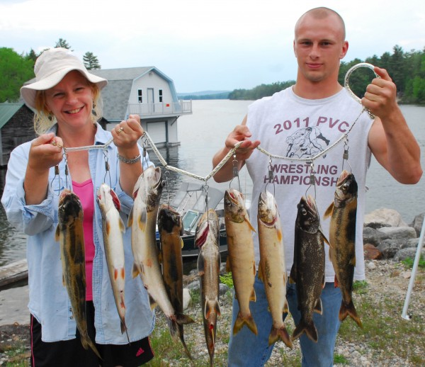 At the boat landing in Grand Lake Stream, Michelle Ferland and her son Ben both of Lincoln, display a catch of Togue they caught Saturday while entered in the West Grand Lake Fishing derby. The weekend derby also encluded Pocomcus Lake, and was designed to reduce the number of small Togue in the two Lakes, leaving healthy fish overall. Evidence gathered from regional fisheries biologist Gregory Burr's scale showed that goal was accomplished.