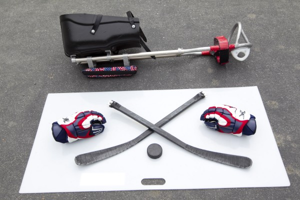 Christy Gardner's sled, hockey sticks and gloves, Thursday, June 13, 2013, in Lewiston, Maine. Gardner is an Army veteran who was just named USA Hockey's Disabled Athlete of the Year. Metal teeth at the ends of each sticks are used to propel the player across the ice.