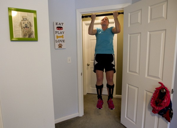 Christy Gardner does pulls-ups in a bedroom doorway, Thursday, June 13, 2013, in Lewiston, Maine.