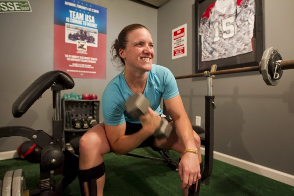Christy Gardner works out with weights in her basement, Thursday, June 13, 2013, in Lewiston, Maine. Gardner was a stand-out athlete at Edward Little High School and CW Post College before entering the Army.