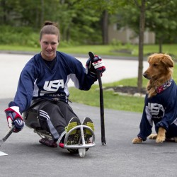 Christy Gardner practices shooting a hockey puck in her driveway as her service dog, Moxie, looks on Thursday, June 13, 2013, in Lewiston, Maine.