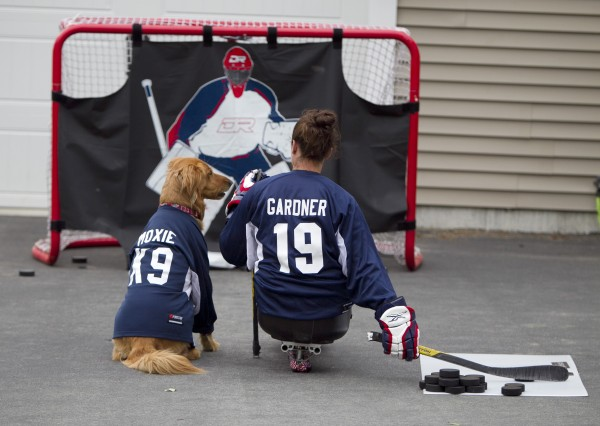 Christy Gardner practices shooting a hockey puck in her driveway as her service dog, Moxie, looks on Thursday, June 13, 2013, in Lewiston, Maine. Gardner plays sled hockey for the US Women's national Team and the mostly male USA Warriors.