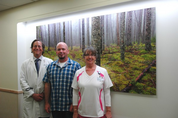 "Photograph ""Acadia Woods,"" pictured with (from left) Dr. Philip Brooks, Patrick Downey, and Jayne Wixon."
