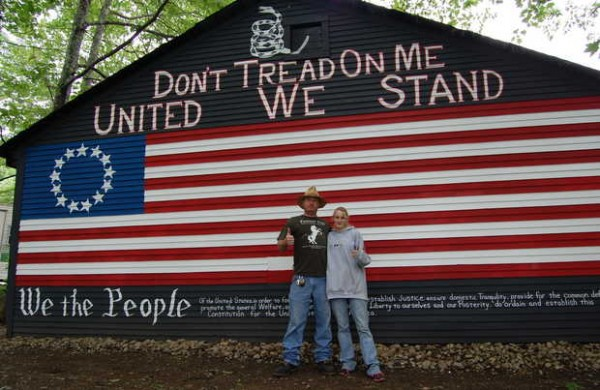 Benjamin Jacques and his girlfriend, Samantha Bell, stand front of a painting of an early U.S. flag on the back of garage that was spray-painted with black paint on June 20. He is offering a $500 reward for the &quotcapture and conviction&quot of the person responsible.