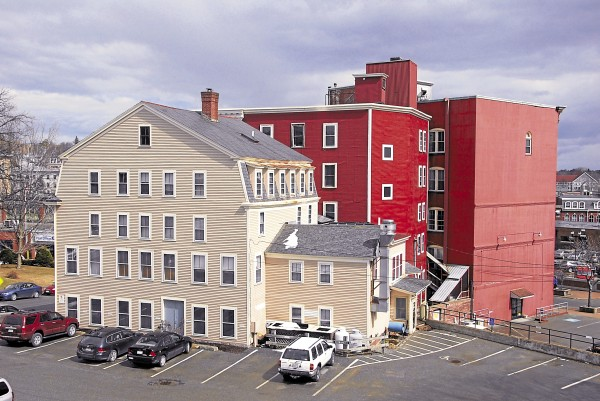 The Bangor-based House Revivers rehabilitated the block encompassing 84-116 Hammond St. in a project made financially possible by federal tax credits for rehabilitating historic buildings. The buildings involved in the project were the tan wood-frame structure (left) and the bright red building (center). The block once housed the Bangor Furniture Co.