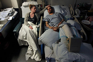 Jen Regan, fiancee of Boston Marathon bomb victim and subsequent amputee Marc Fucarile, strokes his forehead as he sleeps in his hospital bed at Mass General Hospital on a Monday evening in May three weeks following the marathon bombing. Earlier in the day, he had yet another surgery.