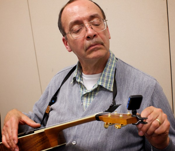 Terry Swift tunes up before playing with the Falmouth Library Ukulele Ensemble, better known as the FLUKES, on a recent Wednesday night.