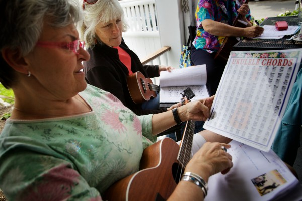 Peaks Island Ukulele Group members Jean Ashmore (left) and Cheryl Higgins look up a G sharp chord wile rehearsing for a gig at a senior luncheon on the island.