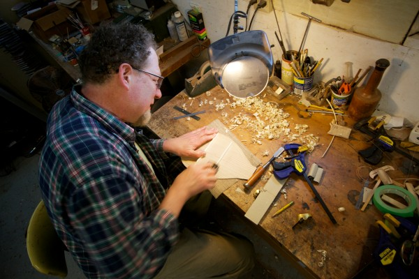 Joel Eckhaus, a South Portland luthier, planes a back brace for a canoe paddle-shaped ukulele he calls a &quotpaddlelele.&quot