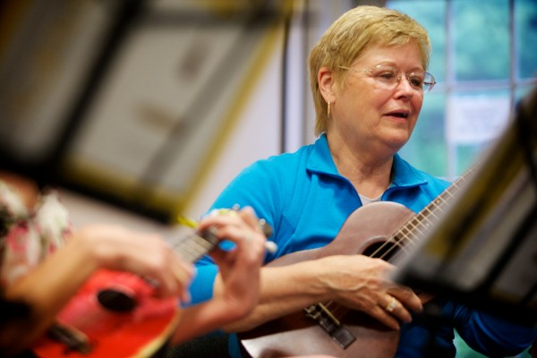 Carrie Peterson strums and sings with the Falmouth Library Ukulele Ensemble, better known as the FLUKES, on a recent Wednesday night.