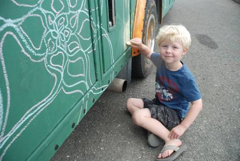 Three-year-old Josh Harvell of Presque Isle works with chalk on the Wintergreen On Wheels (WOW)/TAMC in Your Town Mobile on Thursday, June 20, 2013. The first of its kind art studio on wheels made its debut in Presque Isle last week as part of its mission to bring art and health care related activities to communities throughout Aroostook County.