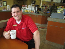 Jamie Myers sits in his Tim Horton's franchise on Broadway in Bangor on Saturday. The Canadian chain has carved out a place for itself in Maine's increasingly competitive and crowded coffee market.