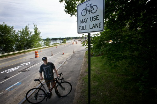 Jay Riley stands with his bike at the Portland side of the Martin's Point Bridge Thursday morning, which is undergoing construction. Riley said he was nearly run off the road by television fisherman Capt. Jim Harkins of Atlantic Adventures on Monday. A video of Harkins verbally abusing Riley went viral on the internet and has cost Harkins his sponsors.