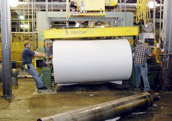 Workers at Lincoln Paper and Tissue LLC of Lincoln move a giant roll of paper onto a machine at the mill on March 11, 2011.