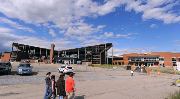 People walk past the partially demolished Bangor Auditorium to the newly completed Cross Insurance Center for the Bangor High School 2013 graduation ceremony.