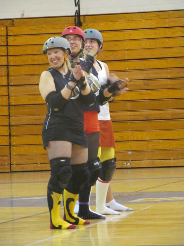 Skaters from the Central Maine Derby team clap as they watch their teammates demonstrate how to play roller derby to a group of incoming freshmen students Wednesday morning in Puiia Auditorium at Mountain Valley High School. From left to right, using their derby nicknames, are Kitty Shreds, Vile Lynn and Mauly Momentum.