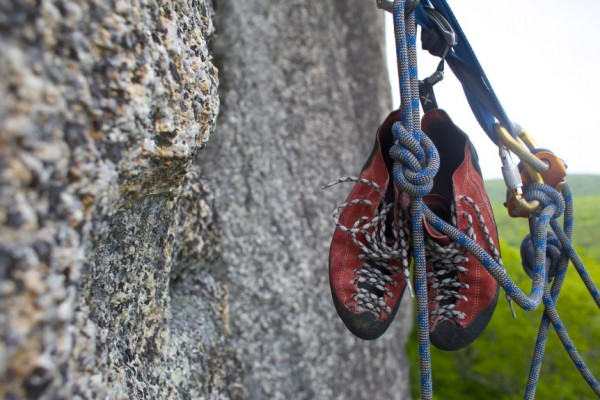 Jared Garfield, Manager of Rental Equipment and Repairs at the Mainebound Adventure Center, hangs his 5.10 climbing shoes and belays other climbers barefoot from an anchor on the 5.7+ route Highlander at Eagle Bluff in Clifton, Maine.